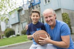 Wizerunek młody człowiek i jego syn bawić się koszykówkę fotografia stock
