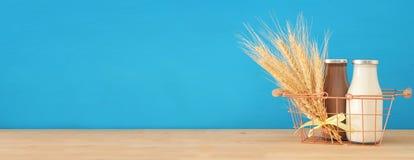 wizerunek mleko i czekolada w koszu z banatką nad drewnianym tłem stołu i pastelu Symbole żydowski wakacje - Shavuot Obraz Stock
