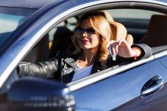 Wizerunek na stronie młoda blond kobieta siedzi w samochodzie z kluczami zdjęcie royalty free