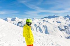 Wizerunek od plecy sporty obsługuje być ubranym hełm na śnieżnym skłonie Zdjęcia Royalty Free