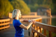 Wizerunek od tylnych sporty kobiet spojrzeń przy zegarem na ręce, stoi na drewnianym moście w parku na lecie zdjęcia stock