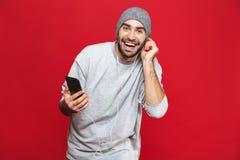 Wizerunek odizolowywający nad czerwonym tłem atrakcyjny mężczyzna 30s słucha muzyka używać słuchawki i telefon komórkowego, obrazy royalty free