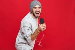 Wizerunek odizolowywający nad czerwonym tłem pozytywny mężczyzna 30s słucha muzyka używać słuchawki i telefon komórkowego, obrazy royalty free