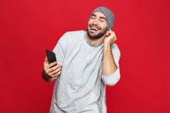 Wizerunek odizolowywający nad czerwonym tłem przystojny mężczyzna 30s słucha muzyka używać słuchawki i telefon komórkowego, fotografia stock