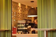 Wizerunek odpierający z żeńskim pracownikiem przy fastem food z widokiem kawowi szkła, maszyny i dekoracyjna ściana wewnętrzna po Obrazy Stock