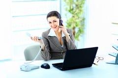 Młoda pracodawca patrzeje kamerę pracuje w biurze podczas gdy planistyczny Fotografia Stock