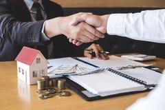 Wizerunek pomyślna transakcja nieruchomość, maklera i klienta chwiania ręki zatwierdzał podaniową formę, po tym jak podpisujący k obraz royalty free