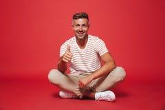 Wizerunek pozytywny mężczyzna 30s w pasiastej koszulce ono uśmiecha się, podczas gdy sitt fotografia royalty free