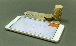 WIZERUNEK PRZEDSTAWIA PIENIĘŻNEGO KALKULACYJNEGO UŻYWA SMARTPHONE kalkulatora Z INDIA waluty monetami W CIEMNYM tle Fotografia Royalty Free