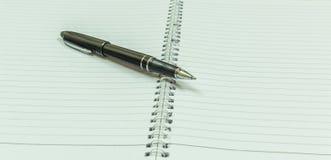 Wizerunek przedstawia pustego ślimakowatego notatnika z czarnym rocznika penImage przedstawia pustego ślimakowatego notatnika z c Obraz Stock