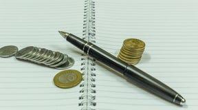 Wizerunek przedstawia pustego ślimakowatego notatnika z czarnym rocznika piórem Obrazy Royalty Free
