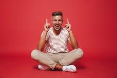 Wizerunek przystojny mężczyzna 30s w pasiastej koszulce wskazuje palce up obrazy royalty free