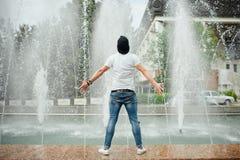 Wizerunek przystojny młody brodaty rozważny mężczyzna w lato odzieżowej pozycji przed piękną fontanną obrazy royalty free