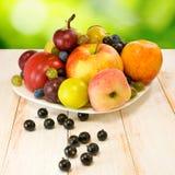Wizerunek różnorodne owoc na stole na zielonym tle Zdjęcia Stock