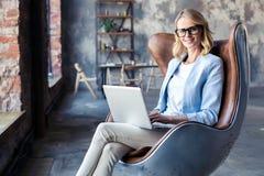 Wizerunek rozochocona biurowa kobieta z blondynem w biznesowym odzieży obsiadaniu na krześle i działanie z laptopu biurem zdjęcie stock
