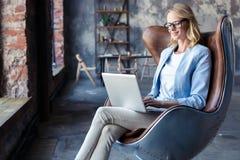 Wizerunek rozochocona biurowa kobieta z blondynem w biznesowym odzieży obsiadaniu na krześle i działanie z laptopu biurem obrazy stock