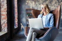 Wizerunek rozochocona biurowa kobieta z blondynem w biznesowym odzieży obsiadaniu na krześle i działanie z laptopu biurem zdjęcia stock