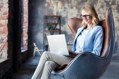 Wizerunek rozochocona biurowa kobieta z blondynem w biznesowym odzieży obsiadaniu na krześle i działanie z laptopu biurem fotografia royalty free