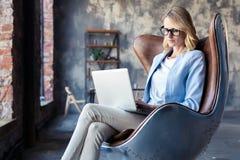 Wizerunek rozochocona biurowa kobieta z blondynem w biznesowym odzieży obsiadaniu na krześle i działanie z laptopu biurem obrazy royalty free