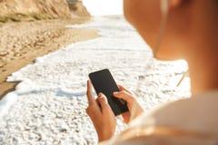 Wizerunek rozochocona dziewczyna 20s jest ubranym słuchawki używać telefon komórkowego, podczas gdy chodzący nadmorski obraz royalty free