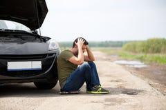 Wizerunek sfrustowany mężczyzna obsiadanie obok łamanego samochodu z otwartym kapiszonem zdjęcie stock