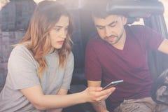 Wizerunek skoncentrowani par spojrzenia przy telefonem komórkowym, zegarek wideo online podczas gdy być w ruchu drogowego dżemu,  obraz royalty free