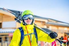 Wizerunek sportive mężczyzna w hełmie z nartami na jego ramię przeciw budynku tłu fotografia stock