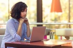 Wizerunek szczęśliwa kobieta używa laptop przy kawiarnią podczas gdy siedzący obraz royalty free