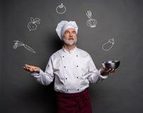 Wizerunek szefa kuchni heblowanie co gotowa? na szarym tle Szefa kuchni g??wkowanie obraz royalty free
