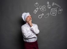 Wizerunek szefa kuchni heblowanie co gotowa? na szarym tle Szefa kuchni g??wkowanie obrazy stock