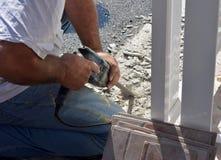 Wizerunek trzyma ceramicznej płytki świderu maszynę mężczyzna pracownik podczas gdy wiertnicze stare płytki Obraz Stock