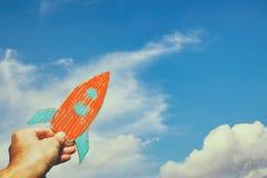 Wizerunek trzyma rakietę przeciw niebu męska ręka wyobraźnia i sukcesu pojęcie Obraz Royalty Free
