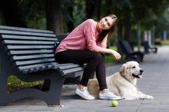 Wizerunek uśmiechnięty dziewczyny obsiadanie na ławce, psi aporter Obrazy Stock