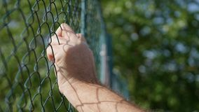 Wizerunek z mężczyzna rękami na Kruszcowym ogrodzeniu zdjęcia royalty free