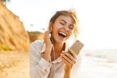 Wizerunek z podnieceniem dziewczyna 20s jest ubranym słuchawki śmia się telefon komórkowego i używa, podczas gdy chodzący nadmors fotografia stock