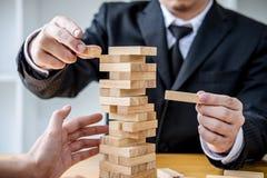 Wizerunki r?ka biznesmeni umieszcza drewnianego blok na i ci?gnie wierza, Alternatywnym ryzyka poj?ciu, planie i strategii, wewn? zdjęcia stock