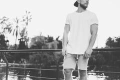 Wizerunku Brodaty Mięśniowy mężczyzna Jest ubranym koszulkę, snapback nakrętkę i skróty w wakacje Białych Pustych, Relaksujący cz Obrazy Stock