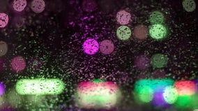 Wizerunku deszcz opuszcza na samochodowym okno miast światła przy nocą w abstrakcjonistycznym bóg w tle płytka głębia pole, gri Obrazy Stock