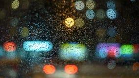 Wizerunku deszcz opuszcza na samochodowym okno miast światła przy nocą w abstrakcjonistycznym bóg w tle płytka głębia pole, gri Zdjęcie Stock