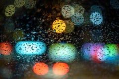 Wizerunku deszcz opuszcza na samochodowym okno miast światła przy nocą w abstrakcjonistycznym bóg w tle płytka głębia pole, gri Zdjęcia Stock
