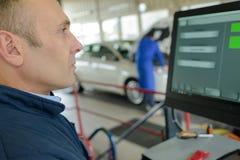 Wizerunku męski mechanik sprawdza opony na komputerze Obrazy Stock