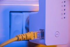 Wkłada etherneta kabel w WiFi extender przyrząd który jest w elec Obrazy Stock