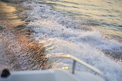 Wlec od motorowej łodzi na rzece przy zmierzchu czasem Zdjęcie Stock