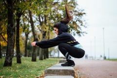 Wman al aire libre en el parque que hace ejercicio de la aptitud salta Foto de archivo libre de regalías