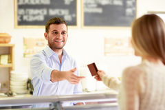 At the counter. Wman with a credit card at the counter Stock Images