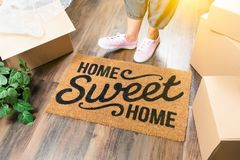 Woman in Pink Shoes and Sweats Standing Near Home Sweet Home Mat. Wman in Pink Shoes and Sweats Standing Near Home Sweet Home Welcome Mat, Boxes and Plant Royalty Free Stock Images