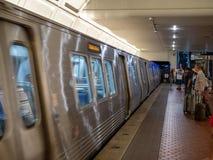 WMATA地铁系列7000训练迅速移动由乘客到遮荫树丛 免版税库存图片