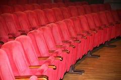 Wnętrza opróżniają czerwonawych kinowych krzeseł siedzenia w skromnym indoors Obrazy Stock