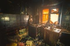 Wnętrze burnt pożarniczym mieszkaniem w budynku mieszkaniowym, palący meble zdjęcia stock