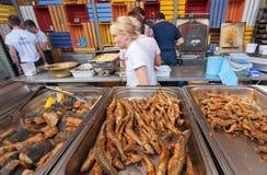 Wnętrze fast food kawiarnia z pracownikami i wysuszony rybi przygotowywający dla jemy, przy popularnym Ulicznym Karmowym festiwal Fotografia Stock